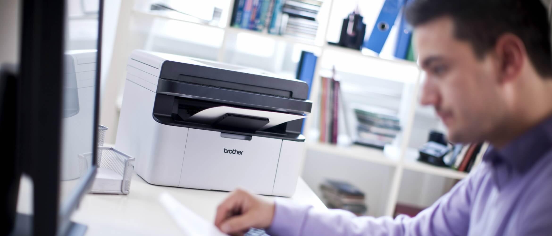 Chico joven en frente de ordenador junto con impresora Brother