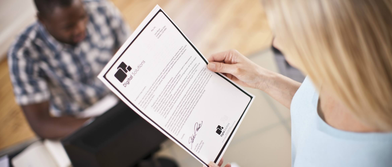 Mujer rubia leyendo un folio impreso