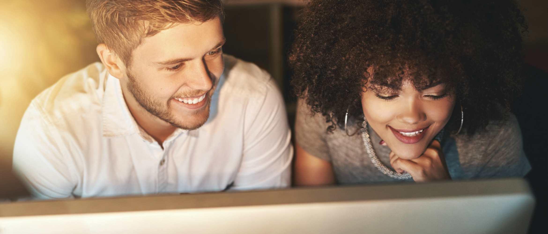 Chico y chica joven frente a pantalla de ordenador