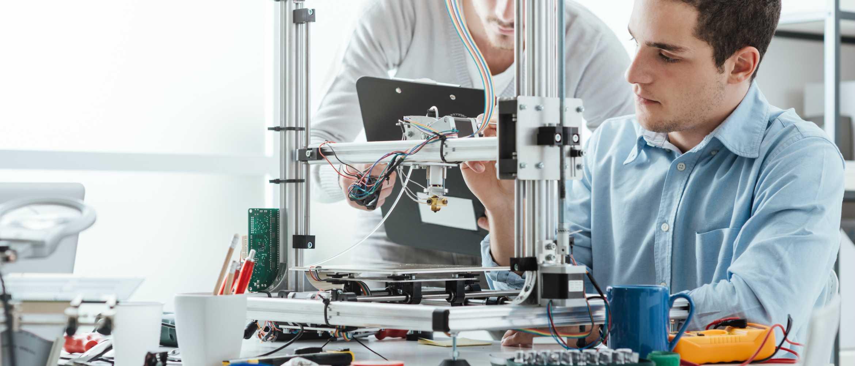 Dos chicos montando impresora 3D