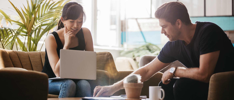 Chica sonriendo con portátil y chico joven sentados en salón de casa