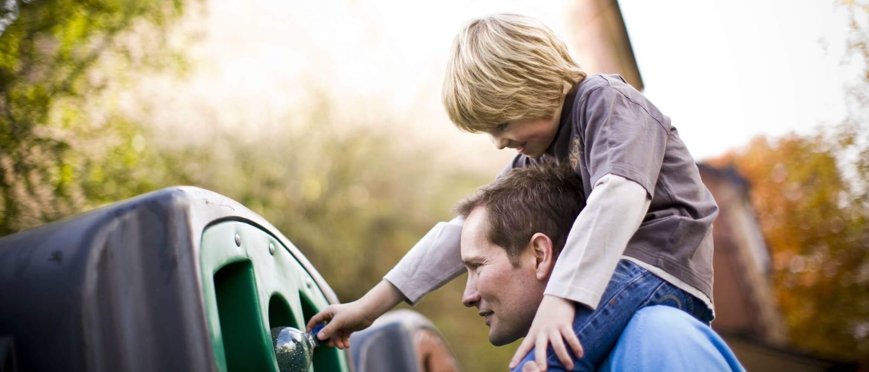 Niño a hombros de su padre tirando botella de plástico en contenedor verde