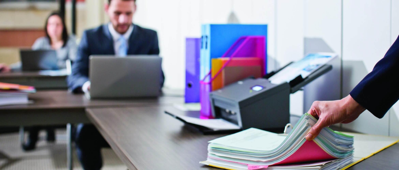 Escáner encima de escritorio junto con archivadores
