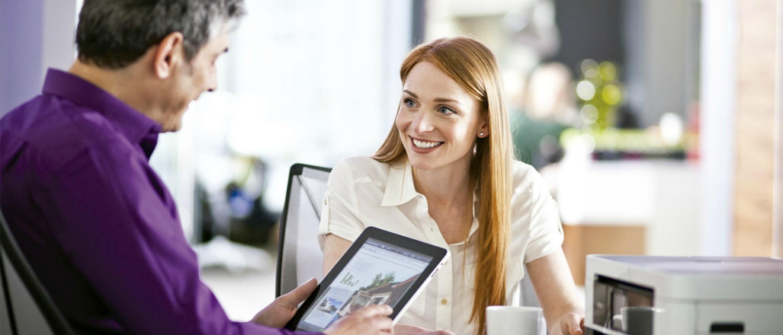 Hombre con tablet y mujer rubia hablando