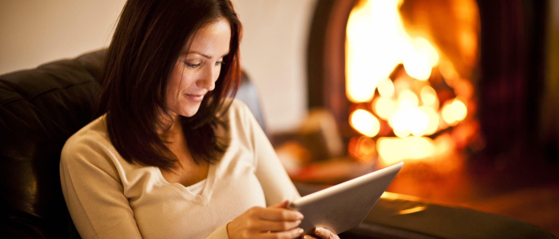 Mujer sentada en sillón mirando tablet