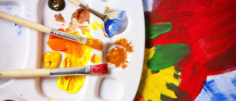 Pinceles manchados de pintura encima de paleta de plástico