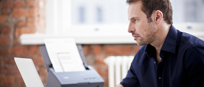 Hombre con camisa azul frente a portatil y junto a escáner