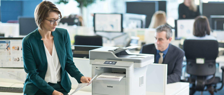 Gente trabajando en oficina y mujer con traje verde sujetando un folio impreso