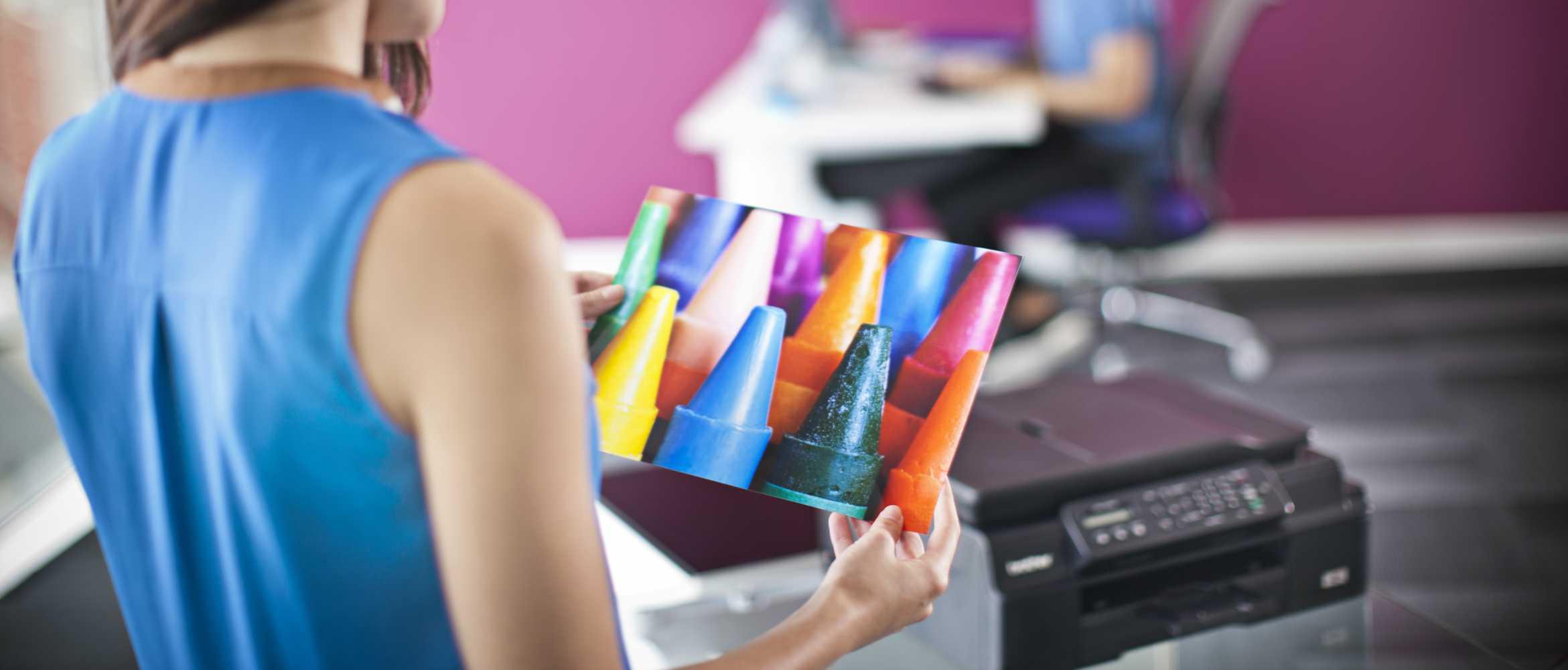 Mujer sujetando folio impreso a color