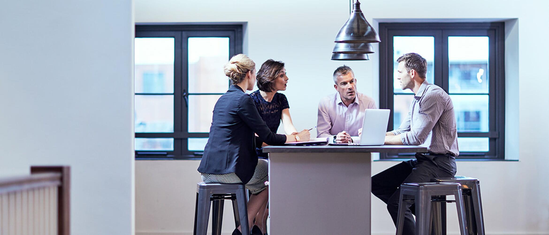 Cuatro personas alreadedor de una mesa mirando un ordenador portátil