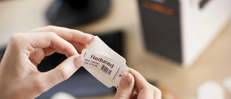Mujer pegando código de barras a etiqueta