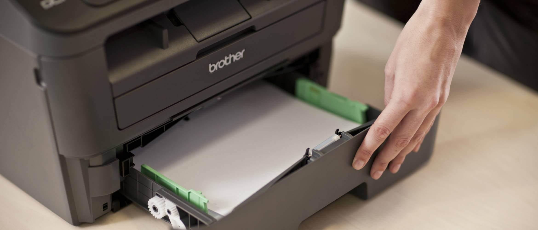 Persona rellenando bandeja de papel de impresora Brother