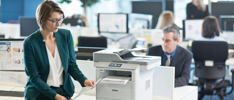 Mujer en oficina junto a impresora multifunción DCP-L6600DW Brother