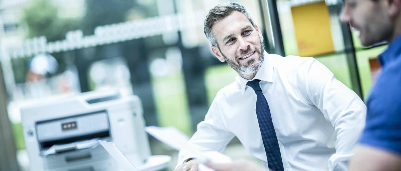 Hombre con camisa y corbata halando con compañero en oficina