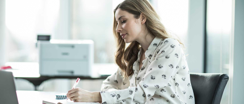 Mujer rubia sentada escribiendo en agenda