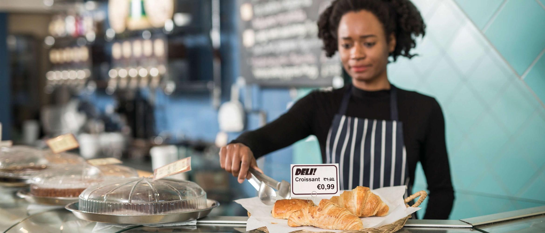 Dependienta junto a croissants con etiqueta de precio