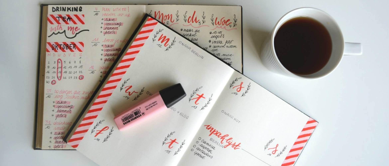 Agenda con marcador encima y taza de café