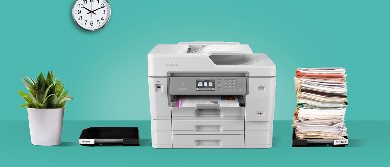 Impresora multifunción Brother junto a material de oficina