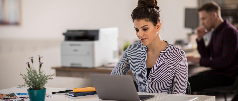 Mujer delante de un ordenador portátil con impresora Brother detrás