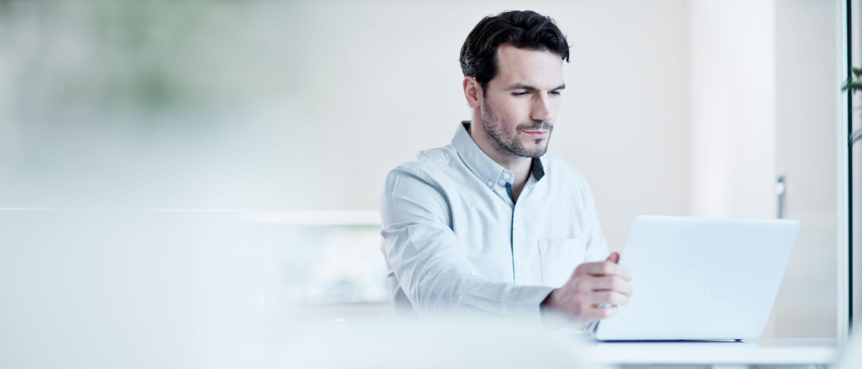 Hombre con barba consultando pantalla de portátil