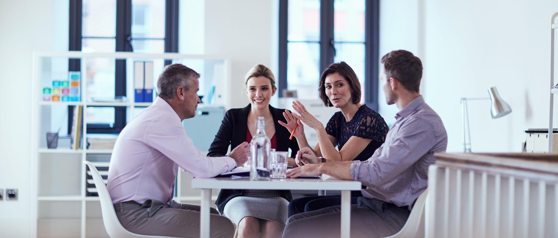 Grupo de personas charlando alrededor de una mesa de trabajo