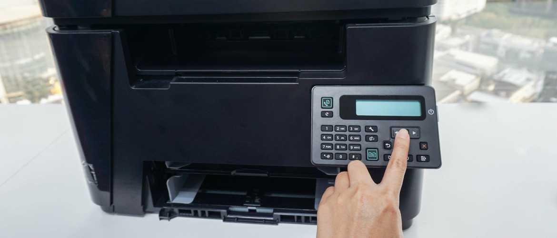 Persona tecleando código en panel de impresora