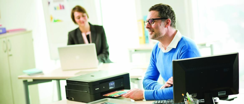 Hombre con jersey azul imprimiendo en oficina