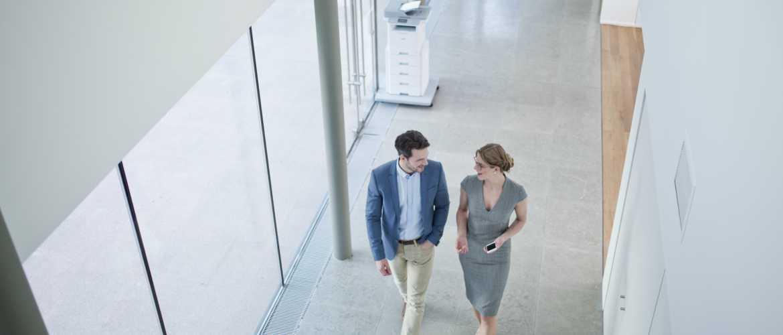 Impresora en pasillo y dos personas pasando
