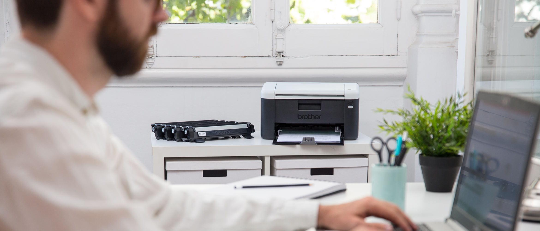Hombre escribiendo en portátil junto a impresora All in box Brother