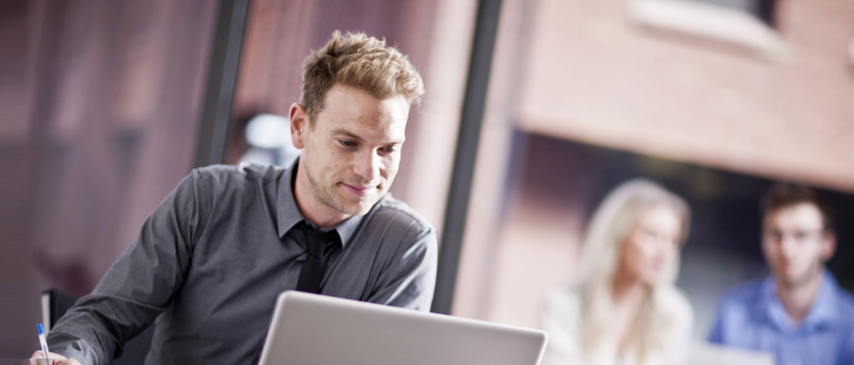 Hombre joven con camisa gris y corbata leyendo pantalla de un portátil