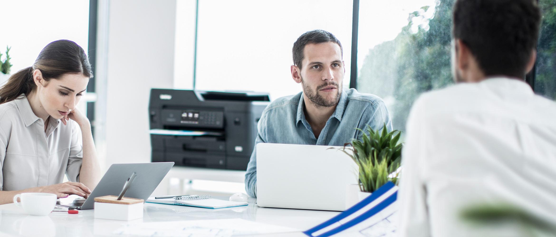 Gente en oficina con impresora multifunción tinta A3 Brother