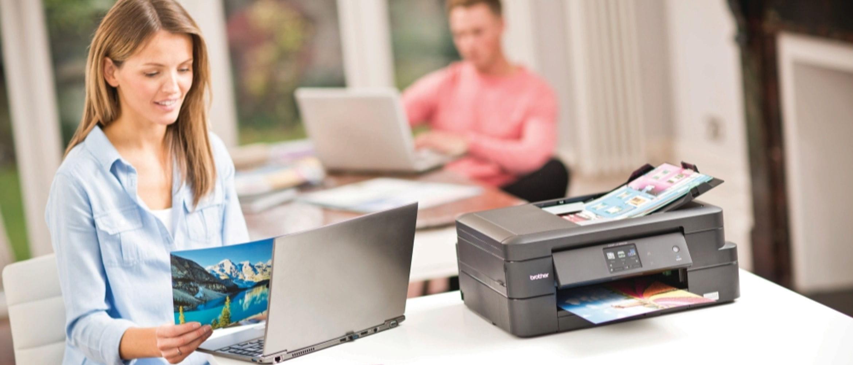 Mujer con portátil e impresora DCP-J785DW Brother al lado