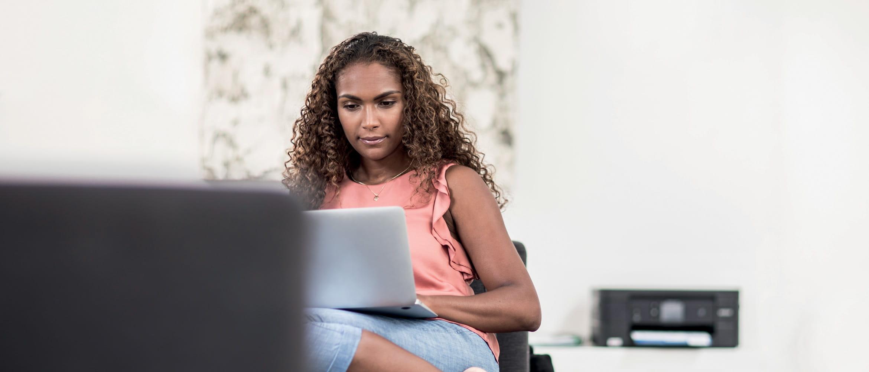 Mujer de pelo rizadd sentada con ordenador portátil