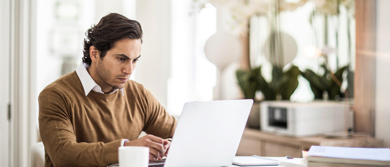 Hombre con jersey marrón utilizando ordenador portátil