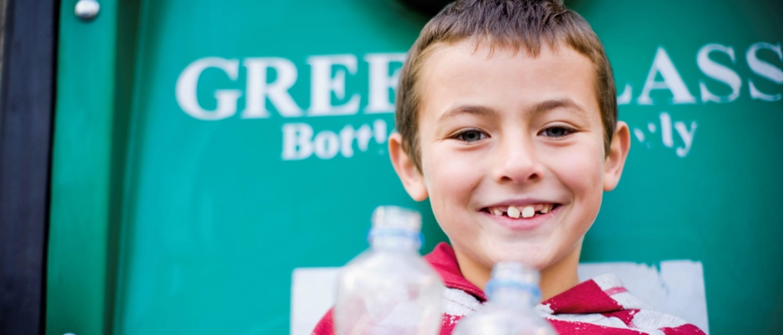 Niño con pelo rubio y botellas de plástico