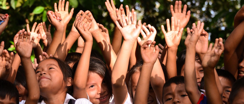 Grupo de niños con las manos en alto
