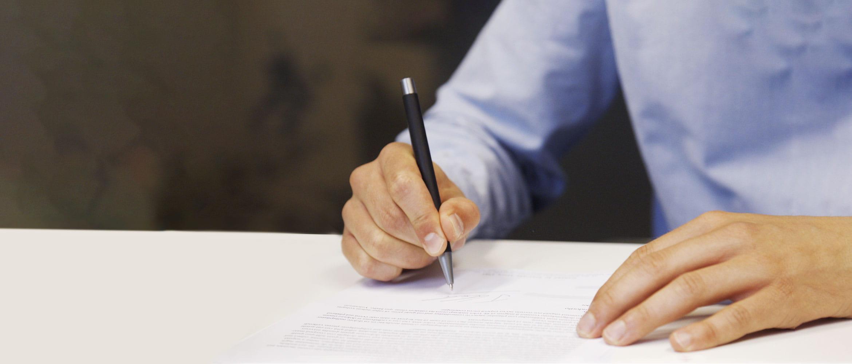 Hombre firmando en hoja