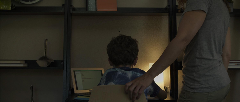 Niño frente a ordenador junto a un adulto