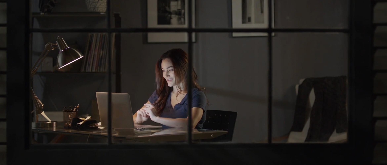 Mujer en habitación frente a ordenador portátil