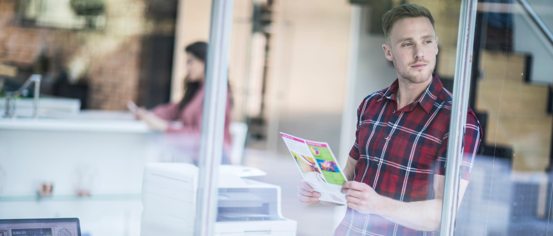Hombre con camisa a cuadros junto a impresora láser color L3000 Brother