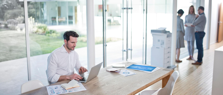 Hombre trabajando en su portátil junto a impresora Brother