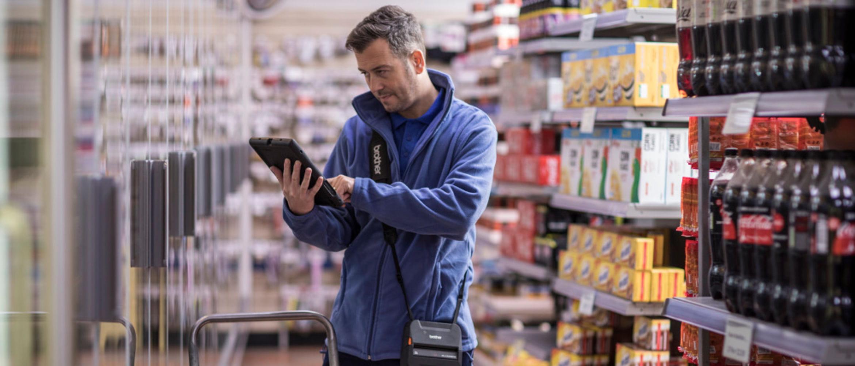 Hombre con tablet e impresora portátil RJ-4 en supermercado