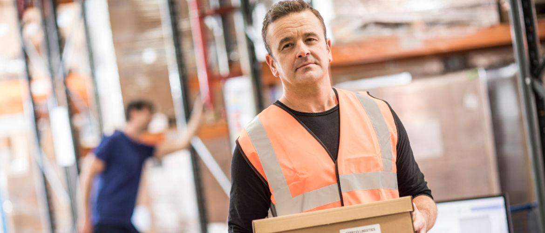 Hombre con chaleco reflectante naranja sosteniendo una caja