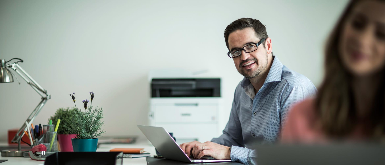 Hombre sentado en su escritorio con impresora láser color Brother al fondo