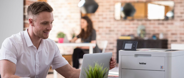 Hombre trabajando en ordenador portátil junto a impresora Brother