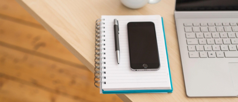Teléfono móvil y bolígrafo sobre cuaderno junto a teclado de portátil