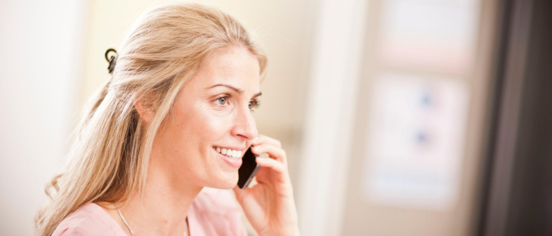 Mujer con pelo rizado hablando por un teléfono móvil