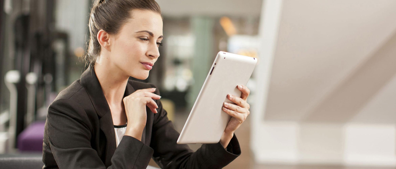 Mujer con chaqueta negra consultando tablet