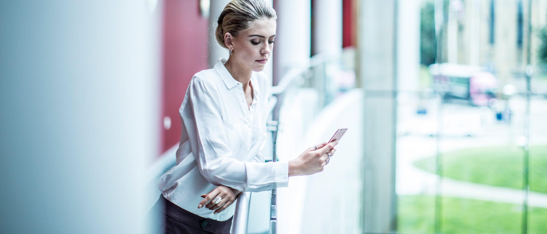 Mujer con blusa blanca consultando su teléfono móvil