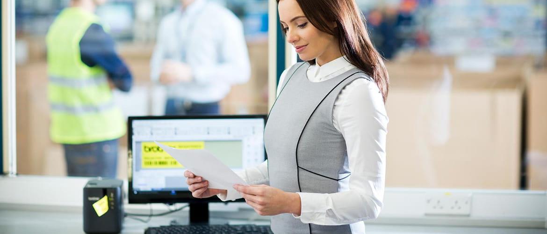 Mujer junto a monitor e impresora de etiquetas Brother